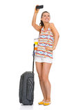 Happy tourist woman with bag taking self photo Stock Photos