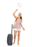 Happy tourist woman with wheel bag throws up hat Royalty Free Stock Photos