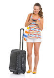 Happy tourist woman with wheel bag writing sms Stock Photo