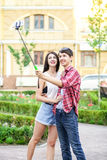 Happy young tourists couple taking a selfie with smartphone on the monopod in city. Stock Photo