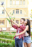 Happy young tourists couple taking a selfie with smartphone on the monopod in city. stock image
