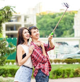 Happy young tourists couple taking a selfie with smartphone on the monopod in city. royalty free stock image