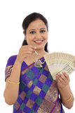 Happy young traditional woman holding Indian currency and house Stock Images