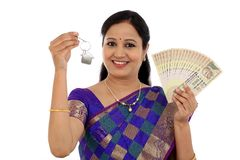 Happy young traditional woman holding Indian currency and house Stock Image