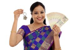 Happy young traditional woman holding Indian currency and house Royalty Free Stock Image