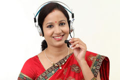 Happy young traditional woman wearing headset Royalty Free Stock Photography