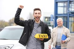 Happy young trainee with taxi roof light. Near car Royalty Free Stock Photography