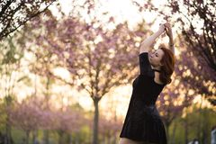 Happy young travel dancer woman enjoying free time in a sakura cherry blossom park - Caucasian white redhead girl - royalty free stock image