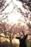 Happy young travel dancer woman enjoying free time in a sakura cherry blossom park - Caucasian white redhead girl - stock image