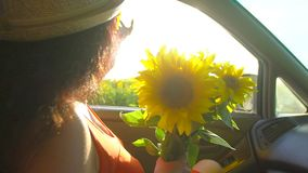 Happy young travel young woman enjoying road trip in summer nature with bouquet of sunflowers. Girl holding arm, puts
