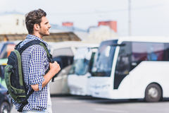 Happy young traveler preparing for departure. Dreamful male tourist is ready to travel. He is looking at bus with inspiration. Man is standing and smiling Royalty Free Stock Image