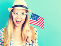 Happy young traveling woman holding American flag Stock Photos