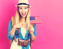 Happy young traveling woman holding American flag Royalty Free Stock Photos