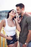Young trendy caucasian couple sharing headphones at outdoors stock photography
