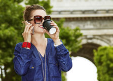 Happy young trendy woman while drinking coffee on Champ Elysees. Get your bags ready for the Paris shopping. happy young trendy woman in sunglasses while royalty free stock image