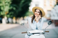 Happy young woman drinking takeaway coffee near her moped and talking phone on city street. Happy young trendy woman drinking takeaway coffee near her moped and Royalty Free Stock Photos