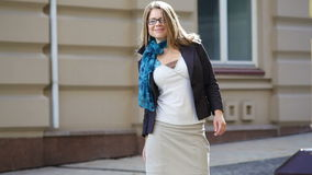 Happy young trendy woman in glasses walking in an urban city.  stock footage