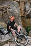 happy young trial biker relaxing on rocks royalty free stock photo