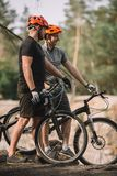 happy young trial bikers standing on cliff stock image