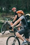 happy young trial bikers standing on rocky cliff with blurred pine forest royalty free stock photo