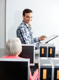 Happy Young Tutor Holding Clipboard In Computer Class. Happy young tutor holding clipboard at whiteboard with senior female student in computer class Stock Photography