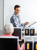 Happy Young Tutor Holding Clipboard In Computer Class. Happy young tutor holding clipboard at whiteboard with senior female student in computer class Royalty Free Stock Photos