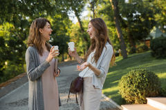 Happy young two women walking outdoors in park drinking coffee Stock Images