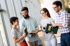 Happy young university students studying with books in library. Group of multiracial people in college library royalty free stock images