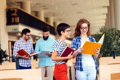 Happy young university students studying with books in library. Group of multiracial people in college library stock image