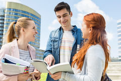 Happy young university students studying outdoors Royalty Free Stock Image