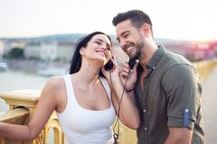 Young urban couple sharing music by headphones at outdoors stock photos