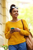 Happy young urban lady walking with mobile phone Royalty Free Stock Photo