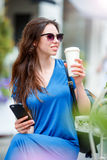 Happy young urban woman drinking coffee in Europe. Caucasian tourist enjoy her european vacation in empty city royalty free stock images