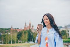 Happy young urban woman drinking coffee in european city. Happy young girl drinking coffee outdoors in the city stock image