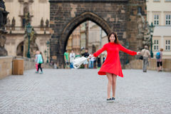 Happy young urban woman in european city on the famous bridge. Caucasian tourist walking along the deserted streets of Stock Image