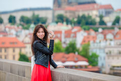 Happy young urban woman in european city on the famous bridge. Caucasian tourist walking along the deserted streets of Royalty Free Stock Image