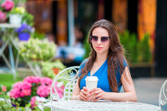 Happy young urban woman with modern mobile and coffee at outdoor cafe in Europe. Caucasian tourist enjoy her european. Girl caucasian drinking hot drink coffee Stock Image
