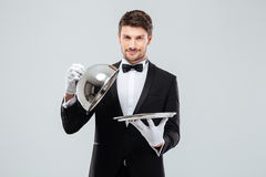 Happy young waiter lifting metal cloche from serving tray. Happy young waiter in tuxedo and bowtie lifting metal cloche from serving tray Stock Photos