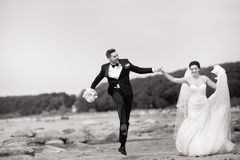 Happy young wedding couple having fun on the beach. Black and white royalty free stock image