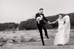 Happy young wedding couple having fun on the beach. Black and white stock image
