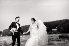Happy young wedding couple having fun on the beach. Black and white royalty free stock images
