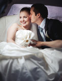 Happy  young wedding couple in limo. Stock Photos