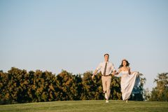 happy young wedding couple running on green meadow stock photography
