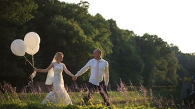 Happy young wedding couple walking with ballooons on the summer field in sunset. Romantic wedding concept