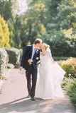 Happy young wedding couple walking together in spring park and kissing on the green lane. Royalty Free Stock Photo