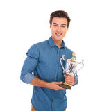 Happy young winner holding his trophy prize and smiles Stock Image