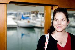Happy young woman. Portrait of happy young woman with yacht marina or harbour in background Royalty Free Stock Photos