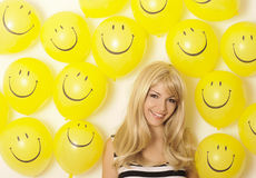 Happy young woman. Surrounded by smiley face balloons Stock Photography