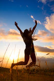 Happy young woman. Young woman joyfully jumping with sunset in backround royalty free stock photo