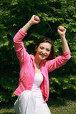 Happy young woman. A view of a happy young woman with a big smile, holding both hands over her head; trimphant expression Stock Photos